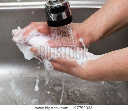 Woman washes her hands with soap under a tap of water .