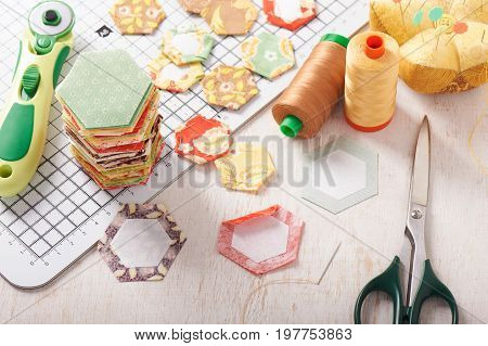 English paper pieced hexagons on white craft mat sewing equipment