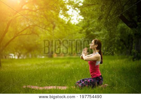 Young female in morning garden practicing yoga in diamond pose. Woman doing vajra-asana, relaxing outdoors. Toned image.