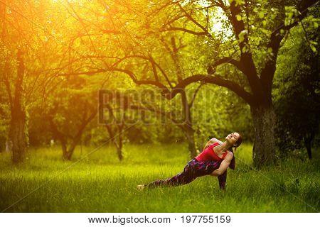 Girl doing extended side angle with grip behind back yoga pose. Exercising yoga in garden. Utthita Parsvakonasana. Toned image.