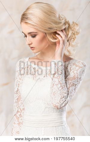 fashionable white gown, beautiful blonde model, bride hairstyle and makeup concept - closeup young romantic lady in wedding festive dress standing indoors on light background, pretty woman posing