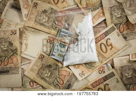 Roll Of Dollar Bills And Cocaine On Top Of 50 Reais Notes