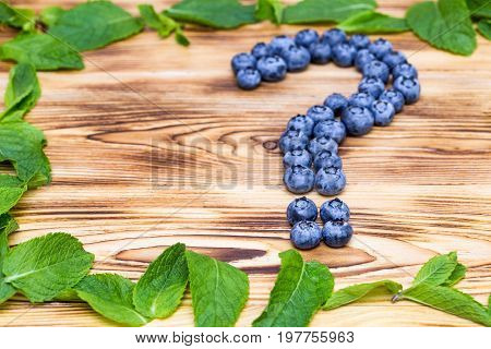 Question sign made of fresh ripe natural blueberries with bright green spearmint frame on a brushed wooden background. Healthy diet  question concept.