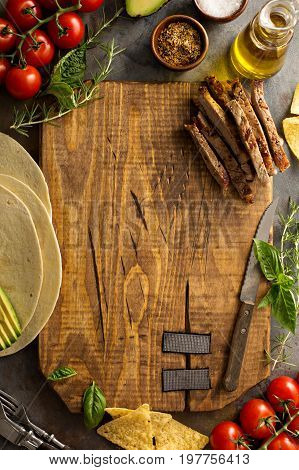 Making tacos with grilled steak, avocado and tomatoes, mexican food concept with copy space, overhead shot