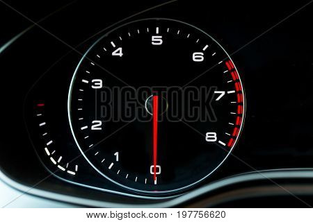Luxury car's dashboard part - tachometer. Red arrow on zero position. Black background and smooth lines. Place for text or signs.