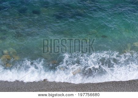 Incredible aerial view from above  of an amazing beautiful sea landscape with turquoise clean transparent water with rocks and rolling waves.