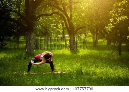 Young sportive woman standing in goddes yoga pose. Woman practicing yoga Utkata Konasana with twisting pose. Toned image.