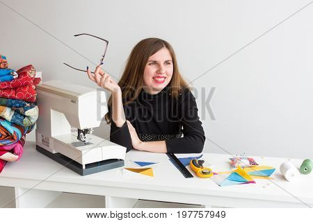 quilting and patchwork - young tailor woman, she took off her glasses, she sits behind a desk with a sewing machine, colored patchwork fabrics, ruler, coils of thread and pin cushion, rotary cutters