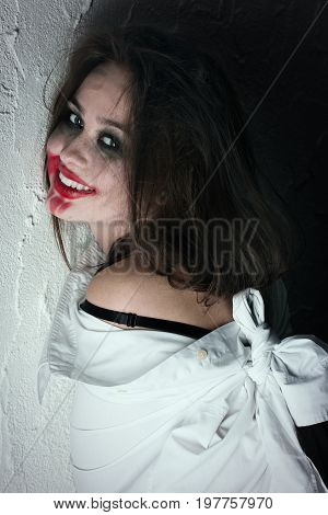 pretty fun crazy girl with fluffy hair and smeared cosmetics near wall looking at camera, laughing