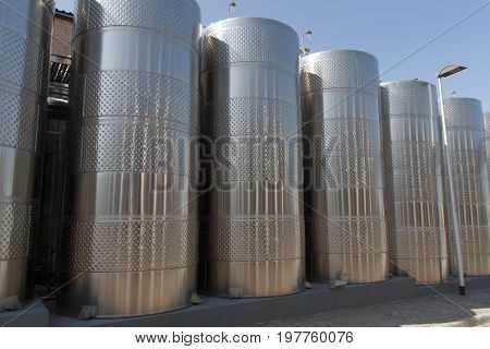 Metal chrome cask for wine photo. Stainless steel pipes and barrels as part of winery equipment