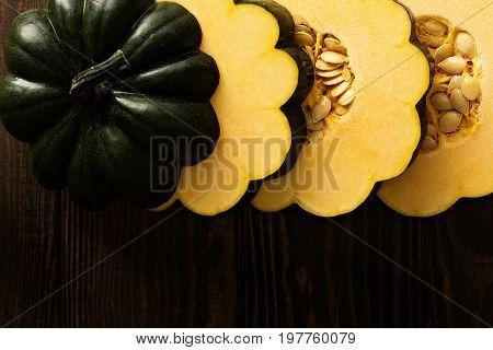 Sliced raw acorn squash on dark background overhead shot