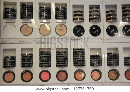 Compact powders and blush on display in a drugstore. (text on display: product information in both English and Dutch)