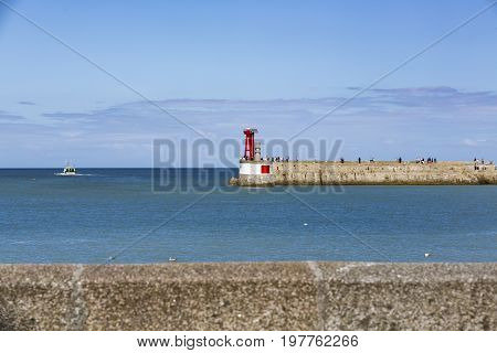 Seawall with red and green lighthouses in Fance Normandy