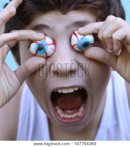 teenager boy with jujube marshmellow eyes smiling open mouth close up portrait