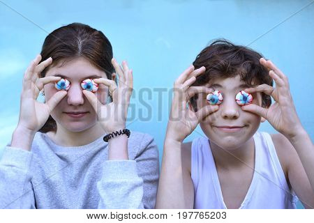 teenager boy and girl with jujube marshmellow eyes smiling open mouth close up portrait