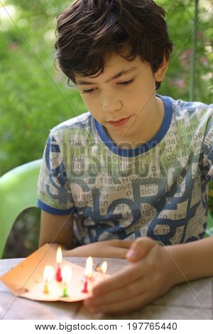 teenager mischievous boy play with candles burn fire close up outdoor photo