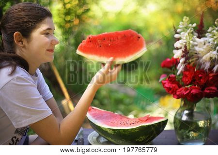 teenager girl eat water melon in summer garden with roses red flowers in vase