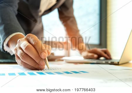 Businessmen are analyzing graphs and using laptop,Employees are analyzing online marketing from charts and laptops.Concepts marketing.