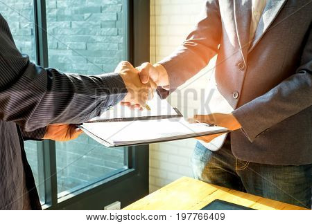 Businessmen are shaking hands and exchanging business documents.People shake hands when reaching agreement.