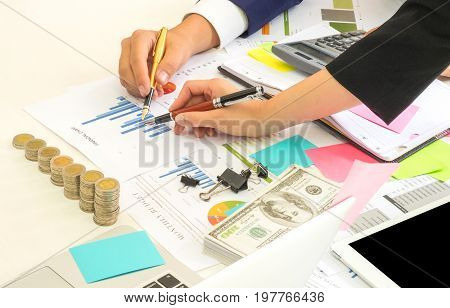 Male and female data analysts are analyzing graph data,Pen in hand male and female data analyst,On the desk there are graphs calculators tablet coins and dollars.