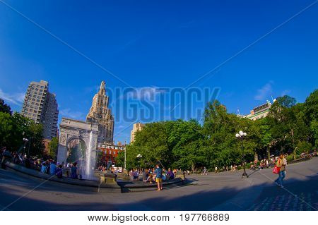 NEW YORK - JULY 22, 2017: Unidentified people enjoying the summer day in the Washington Square Park Arch and fountain, New York, Usa fish eye effect.