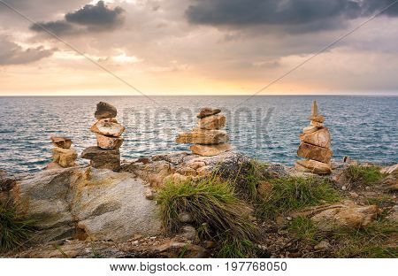 Stacked Stones On A Beach In Thailand At Sunset