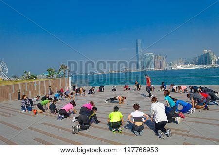 HONG KONG, CHINA - JANUARY 26, 2017: Crowd of people doing Tai Chi Exercising in the morning, with a downton of the city of Hong Kong as background. With a land of 1, 104 km and population of 7 million, Hong Kong is one of most densely populated areas in