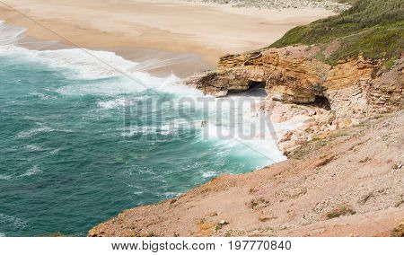 Stunning shoreline with caves and surfing waves near Nazare city Portugal