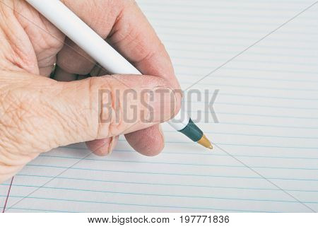 Male left hand ready to start writing on lined paper