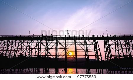 Silhouetted bridge at sunset in Sangkla Thailand