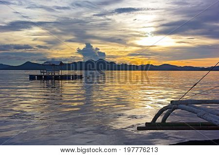 A view from traditional fishing boat with outriggers in lagoon of Coron Island at cloudy sunset. Floating gazebo at sunset with mountain ridges on horizon.