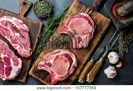 Raw Pork Cutlet Chop For Fry On Grill And Pan With Herbs, Garlic On Wooden Boards, Slate Gray Backgr