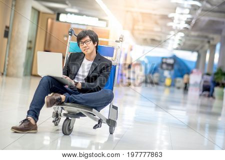 Young asian man working on airport trolley with his laptop computer during waiting for a connecting flight freelance lifestyle and digital nomad concepts