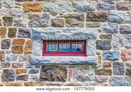 Closeup of small red window with colorful stone European wall