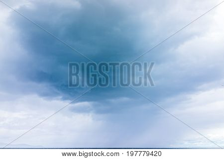 Many white seagulls birds flying in flock group against stormy gray cloud in sky