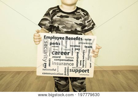 employee benefits concept. Photo for your design. The boy at the wall. Holds a sign in his hand
