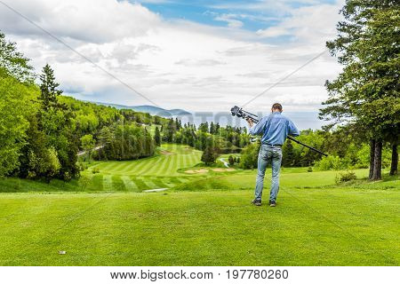 Landscape view of green golf course with hills in summer in La Malbaie Quebec Canada in Charlevoix region with photographer and tripod