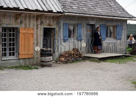 MACKINAW CITY, MICHIGAN / UNITED STATES - JUNE 18, 2017: A costumed interpreter stands outside the door of the Northwest Rowhouse of Fort Michilimackinac, in the Colonial Michilimackinac State Park.