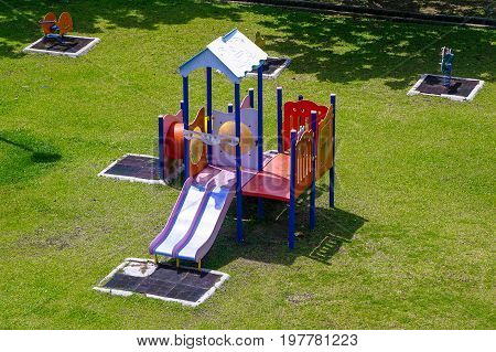 Playground equipment for kids playground on yard for any playground activities at public park with green grass background