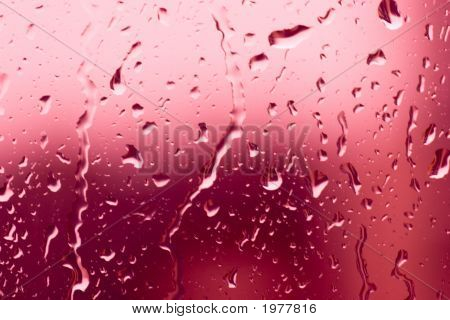 Flowing On Transparent Red Glass Water Drops