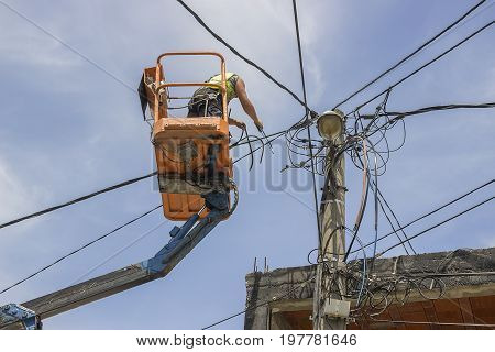 Utility Pole Worker Replacing Cables On An Electric Pole