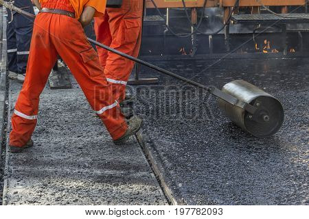 Worker Pushing Hand Roller For Mastic Asphalt Paving