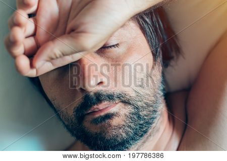 Adult caucasian man sleeping in bed top view of naked male person with his head on the pillow in the morning