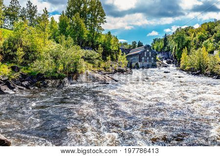 Chicoutimi Canada - June 3 2017: La Pulperie de Chicoutimi Regional Museum Pulp mill in Saguenay Quebec with river and water flowing in summer