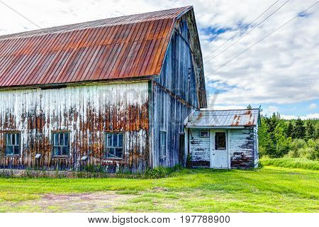 Red Metal Painted Old Vintage Barn Shed House In Summer Landscape Green Grass Field In Countryside