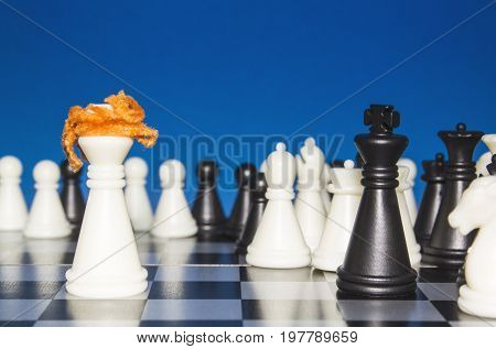 Chess As A Policy. A Lone White Figure With Red Hair Against A Black Figure With A Team. The Public