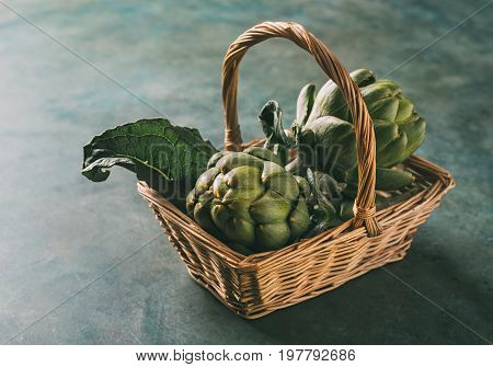 Ripe organic artichokes in a wicker basket on a blue background. Healthy eating.