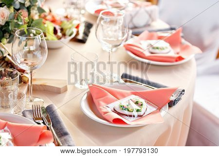 Elegant table setting in wedding. Peach tablecloth and pink napkins. dinner outdoors in the Park