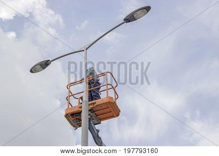 Worker In Lift Bucket Repair Street Light Pole