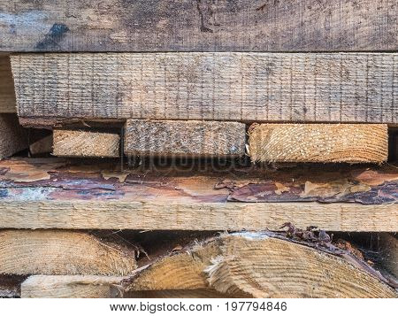 The boards stacked on top of each other. Boards of pine. Lying trimming boards, stack of pine boards on building materials warehouse. Firewood for heating the house and kindling. Wood for the stove